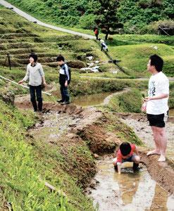 親子で田植え体験をする観光客たち=輪島市白米町で