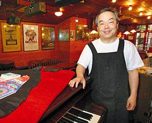 40周年を迎え、ピアノの名器ベーゼンドルファーの前で思い出を語る平賀正樹さん=金沢市柿木畠で