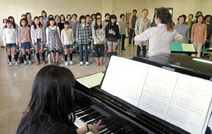 コンサートに向けて練習をする合唱団員と小中学生ら=魚津市新川学びの森天神山交流館で