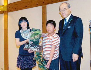 MISIAさんのデザインによる巣箱を谷本知事から受け取る児童=津幡町津幡の県森林公園で
