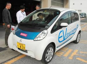宮川さん(左)らから電気自動車の扱い方の説明を受ける職員=豊郷町役場で