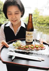 チケット1枚(600円)で提供される「牛たたきサラダ風」とビール=守山市の料亭「魚和」で