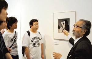 東松さんの写真を紹介する越知さん(右)と愛知大の学生=名古屋市中区の市美術館で