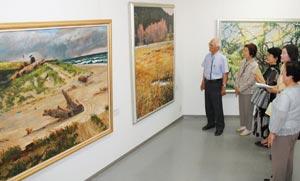 来場者らに作品を解説する白井さん(左)=磐田市の磐田市民ギャラリーで