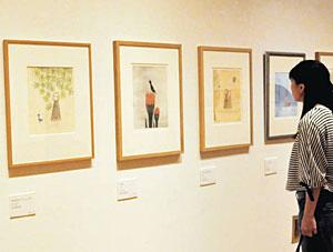 メルヘンチックな南桂子さんの版画に見入る来場者=高岡市美術館で