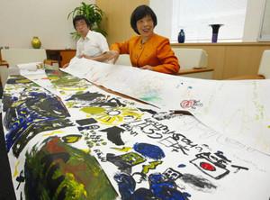 世界の子どもたちが描いた東北激励の絵を見せる近藤さん(右)ら=中日新聞北陸本社で