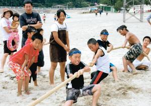 浜辺で綱引きを楽しむ子どもたち=尾鷲市三木里町の三木里海水浴場で