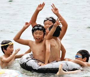 海に入り、歓声を上げる子どもたち=熊野市の新鹿海水浴場で