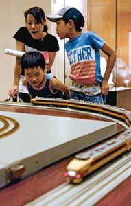 ひた走る鉄道模型に歓声を上げる親子=福井市の県立歴史博物館で