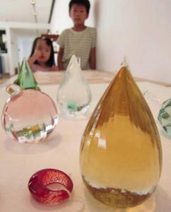 「リングレスト」など、さまざまな色や形のガラス作品が並ぶ作品展=射水市大島絵本館で