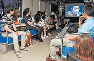 マネキンの首(手前右)が置かれるなどした車内で稲川淳二さんの怪談を聞く乗客=福井市内で