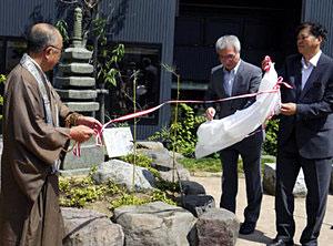 桃妖顕彰の碑の除幕をする出席者=加賀市山中温泉で