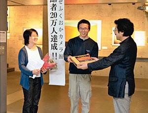 金山館長(右)から入館者20万人目の記念品の写真集を贈られる森さん親子=高岡市福岡町福岡新で