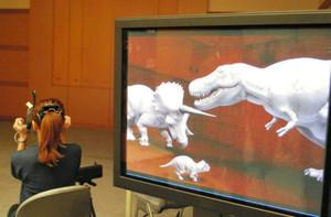 専用の装置を使うと、目の前の実空間に右画面のように恐竜が現れる=勝山市の県立恐竜博物館で