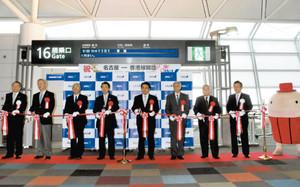 香港線の運航開始を記念してテープカットをする大村秀章知事(左から5人目)ら=中部国際空港で