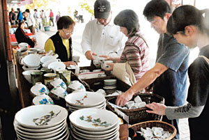 逸品を求め、九谷焼を手に取る人たち=能美市泉台町で