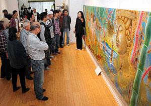 訪れた住民に絵の説明をする八十山さん(右)=小松市村松町で