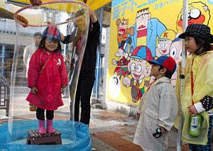 怪物くんツアーでシャボン玉に包まれる体験を楽しむ子ども=氷見市中央町で
