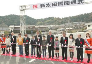 テープカットで新太田橋の完成を祝う尾関市長(左から7人目)や金竜小児童ら=関市で