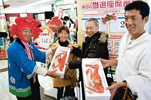 表課長(左)からカニを受け取った高橋さん(右)と、林さん夫妻=能登空港で