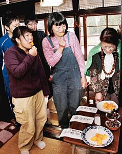 小田さん(右)の解説を聞きながら3種類の柿を味わう訪れた人たち=白山市白峰で