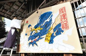 来年の干支「辰」が愛嬌ある表情で描かれた巨大絵馬=日野町の馬見岡綿向神社で