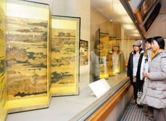 駿府城や浜松城などがリアルに描かれた屏風に見入る人たち=静岡市葵区の静岡市文化財資料館で