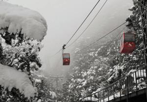 雪深い山肌を行き交うロープウエーのゴンドラ=菰野町の湯の山温泉で