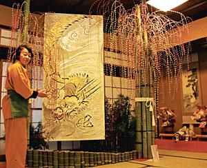 加賀友禅職人が描いた竜の絵とともに飾ったまゆ玉=小松市粟津温泉で