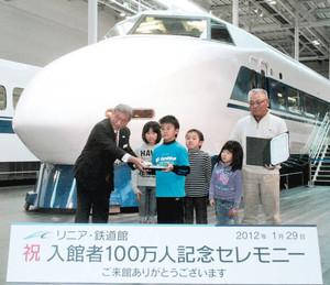 新幹線100系の前で100万人目の入館者として記念品を受け取る鳥居洋治さんと孫たち=名古屋市港区のリニア・鉄道館で