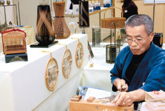 竹ひごを削り駿河竹千筋細工を実演する篠宮さん=浜松市中区の遠鉄百貨店で