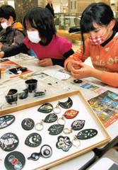 駿河漆器のキーホルダー作りに挑戦する児童たち=浜松市中区の遠鉄百貨店で