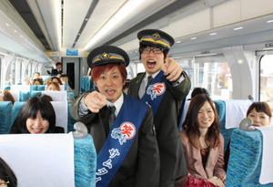 「お笑い列車」で、乗客と一緒に「出発」と叫ぶサムタイムズの2人=名鉄ミュースカイの車内で