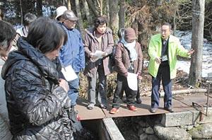 磯部副理事長(右)の案内で弘法池を見学する参加者=白山市釜清水町で