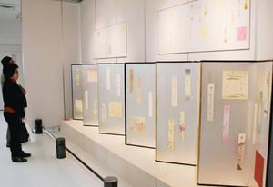 野本さんが直筆で俳句をしたためた色紙や短冊が並べられた会場=白山市千代女の里俳句館で