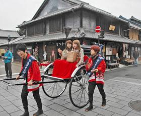お笑いコンビが引く人力車で城下町を巡る観光客