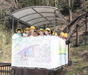中池見湿地を描いた絵がデザインされたスロープカーに乗る咸新小の児童たち=敦賀市樫曲で
