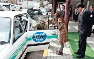本格運行した乗り合いタクシーに乗る利用者=能登町宇出津で