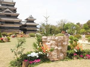天守を背に色鮮やかに飾られた生け花の作品=松本市の国宝松本城本丸庭園で