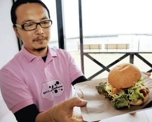 ボリューム感が売りのみそかつバーガーを手にする西辻さん=津市なぎさまちの商業施設ベイシスカで