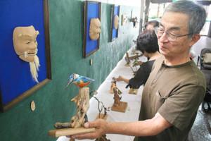 木目を生かした彫刻作品を手にする佐々木梶雄さん(右)=阿久比町中央公民館で