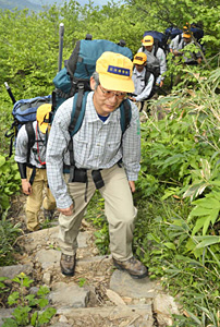 救助装備を背負って白山を登る県警山岳遭難救助隊員=白山の砂防新道で