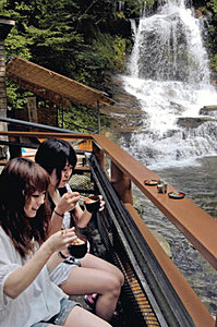 迫力の大滝を楽しみながら、流しそうめんを食べる女性たち=津幡町で
