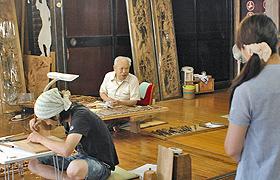 八日町通り沿いの彫刻工房を訪ねる観光客