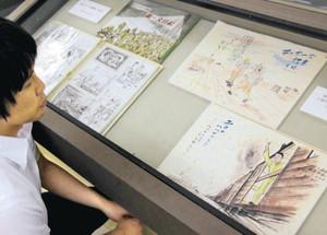 強制労働の体験を絵本風にまとめた冊子などが並ぶ小岩さんの遺作展=揖斐川町上南方の揖斐川歴史民俗資料館で