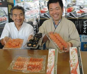 ビワマスの棒ずし、昆布巻き、スモークの新商品を手にする大沢剛人さん(右)と川瀬利弥さん=長浜市役所で
