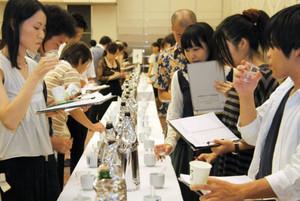 集まった県内の地酒を飲み比べ、味を評価する参加者=大津プリンスホテルで