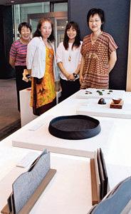 能「紅葉狩」を表現したさまざまな工芸品と制作した会員ら=金沢市広坂の金沢能楽美術館で