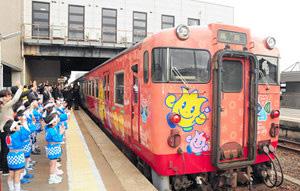 出町幼稚園児や関係者らに見送られ出発するラッピング車両=JR砺波駅で