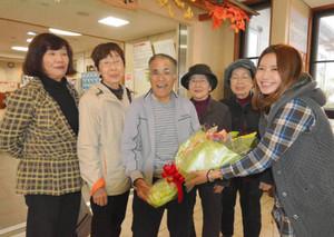 鍋島さん(右端)から記念の花束を贈られる200万人目の入浴者、鈴木さん(左から3人目)=豊根村の「湯~らんどパルとよね」で